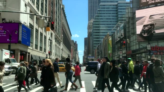 crowds of people walking crossing in new york city with empire state building in the background - 横断歩道点の映像素材/bロール