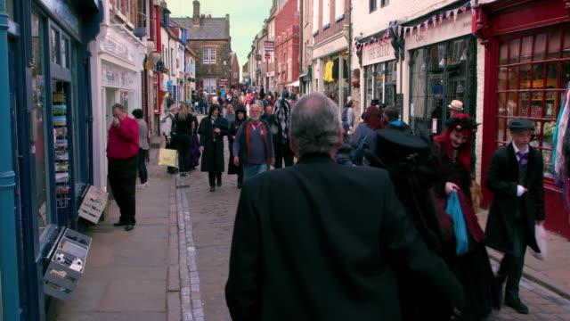 stockvideo's en b-roll-footage met crowds of people walking on cobbled street church street, whitby, north yorkshire, england - kassei
