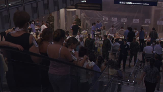 crowds of people wearing armbands ride escalators down to a makeshift clinic. - surgical mask stock videos & royalty-free footage