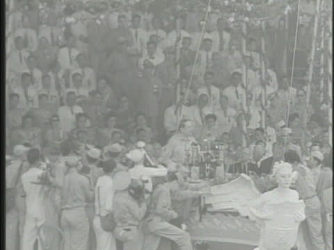 Crowds of Philippine people General Douglas MacArthur at ceremony in Manila Philippines MacArthur speaking ' a new nation is born in the struggle of...
