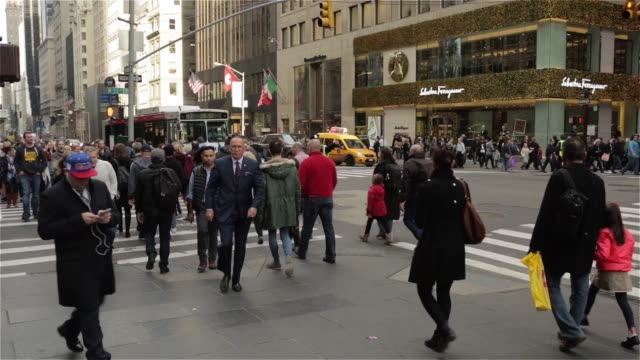 crowds of shoppers walk down the sidewalks of fifth avenue in new york city, new york during the holiday shopping season on december 14th, 2015... - fifth avenue stock videos & royalty-free footage