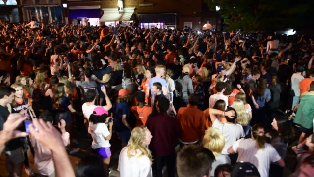 vidéos et rushes de crowds of students gather in the streets of charlottesville to celebrate the win 85-77 over texas tech. - charlottesville