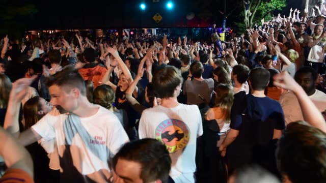 crowds of students gather in the streets of charlottesville to celebrate the win 85-77 over texas tech. - バージニア大学点の映像素材/bロール