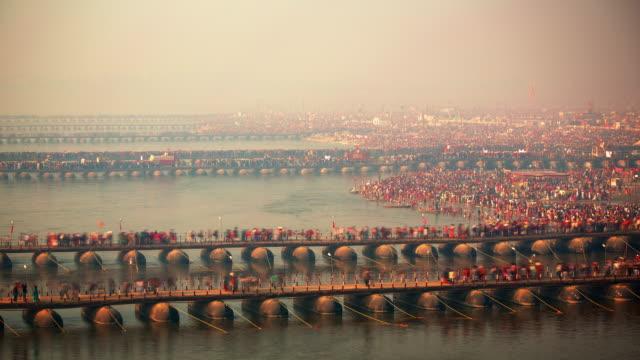 crowds of thousands throng the riverbank and bridges at the kumbh mela - acqua santa video stock e b–roll