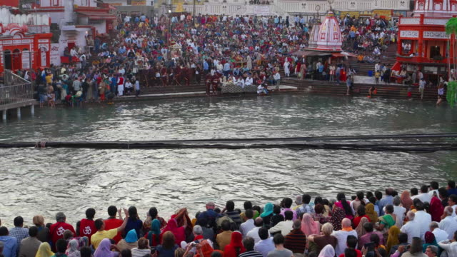 Crowds of tourists and pilgrims seated and getting ready to watch the evening aarti, traditional religious ceremony, at the banks of the holy Hindu river Ganges in Haridwar, India