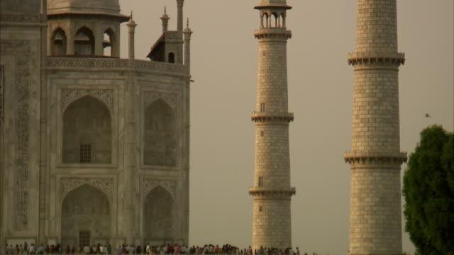 crowds of tourists are dwarfed by the taj mahal. - 史跡めぐり点の映像素材/bロール