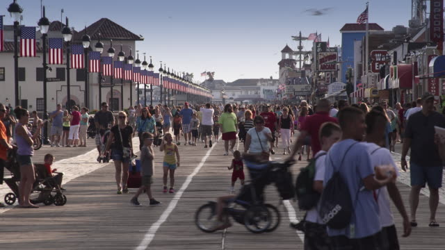 vídeos y material grabado en eventos de stock de crowds of tourists walk down a jersey boardwalk in ocean city nj on a summer day.  the american flag lining the boardwalk and people spend time with their families. - bulevar