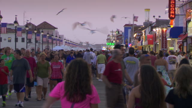 Crowds of tourists walk down a Jersey Boardwalk in Ocean City NJ on a summer evening.