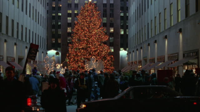 crowds of traffic and pedestrians pass rockefeller center at christmas time. - rockefeller center christmas tree stock videos & royalty-free footage