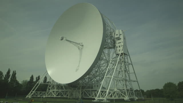 crowds of visitors are dwarfed by the enormous lovell telescope radio dish at the jodrell bank observatory, cheshire, uk. - communication stock videos & royalty-free footage