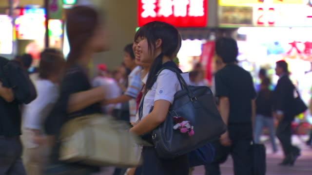 MS PAN SELECTIVE FOCUS Crowds of young people crossing Shibuya street at night, Shibuya, Tokyo, Japan