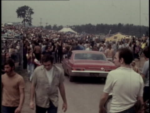 crowds of young people swarm max yasgur's farm in bethel, new york, for the 1969 woodstock music and art fair. - young adult stock videos & royalty-free footage