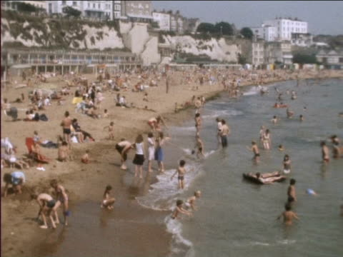 crowds on beach sunbathe and play in sea during heatwave 1976 - 1976 stock-videos und b-roll-filmmaterial