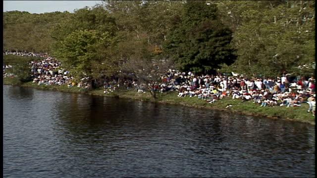 crowds on shore watching head of the charles regatta in boston - チャールズ川点の映像素材/bロール