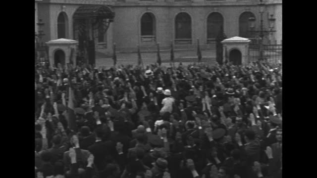 crowds outside royal palace in bucharest / crowds with arms raised in salute; tilt up to king carol ii standing on balcony with arm raised / king /... - romania stock videos & royalty-free footage
