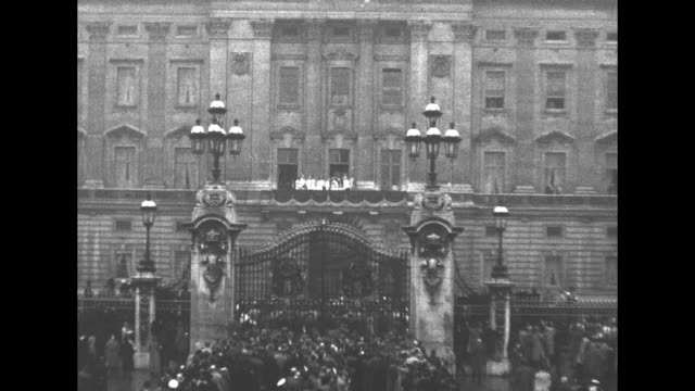 ws crowds outside the gate face buckingham palace where royal family members stand on balcony in background after coronation of george vi / queen... - 1937 stock-videos und b-roll-filmmaterial
