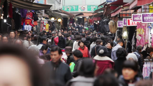 ls crowds pack a shopping street in namdaemun market / seoul, south korea - south korea stock videos & royalty-free footage