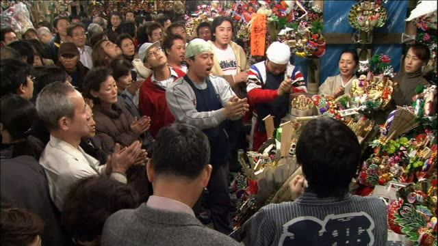 crowds participate in ceremonial hand clapping at the ohtori shrine.  tori-no-ichi - shrine stock videos and b-roll footage