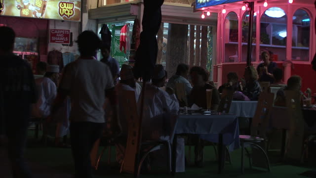 MS Crowds pass by people seated on tables outside in Juice Center  / Muscat, Oman