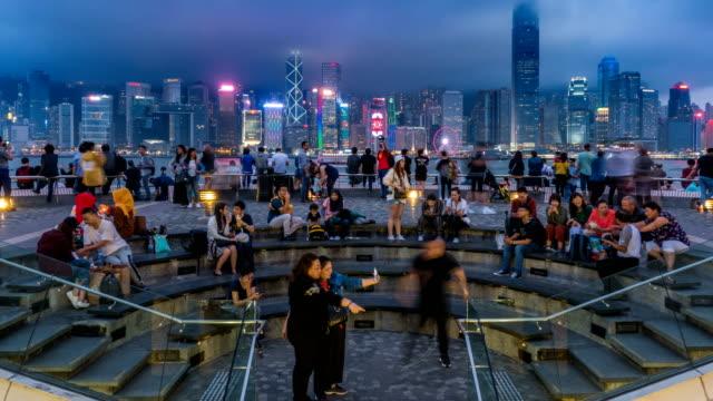 4k t/l - folla di persone in attesa di una sinfonia di luci al victoria harbour di hong kong - victoria hong kong video stock e b–roll
