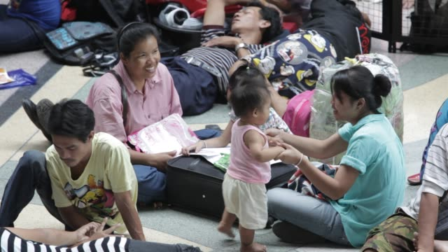 crowds queue for train tickets and sleep on the floor of bangkok train station as they attempt to leave the city before expected flooding on october... - bronek kaminski stock videos & royalty-free footage