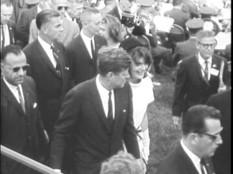 / crowds running to hear speech large crowd gathered president and jackie kennedy walk onto outdoor stage jackie stands with lyndon johnson ws stage... - attentat auf john f. kennedy stock-videos und b-roll-filmmaterial