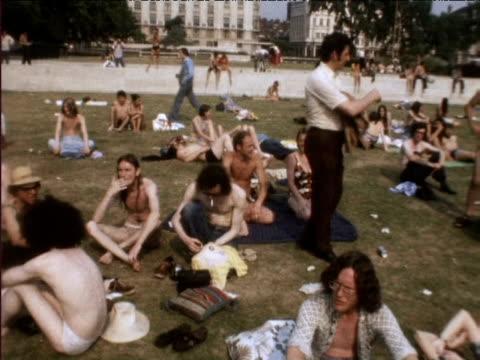 vídeos de stock, filmes e b-roll de crowds sunbathe in park during heatwave 1976 - onda de calor fenômeno natural