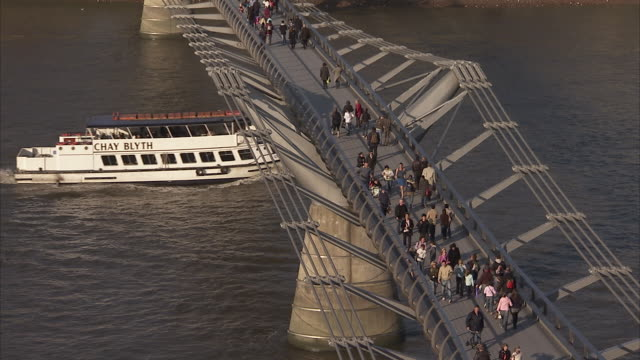 Crowds walk across the Millennium Bridge as a ferry cruises the River Thames. Available in HD.