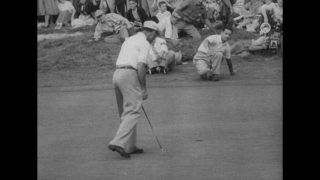 crowds walk on golf course at augusta national golf club shot framed by trees in foreground / ben hogan putts golf ball into hole to win masters... - golf links stock videos & royalty-free footage
