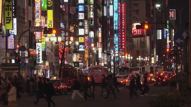 ws crowds walking below neon lights at shinjuku street / tokyo, kanto, japan - japan stock videos & royalty-free footage