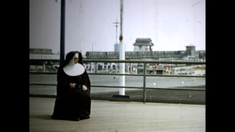 crowds walking past international flags and trylon and perisphere / nun in habit sitting outdoors, elevated train traveling in bg / people waiting,... - new york world's fair stock videos & royalty-free footage