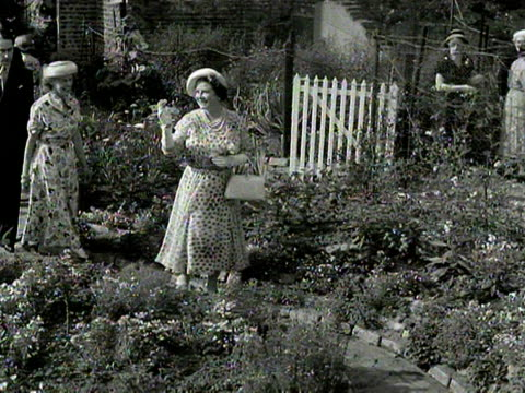 crowds watch as the queen mother takes a tour of an ornamental garden 1954 - queen dowager stock videos and b-roll footage