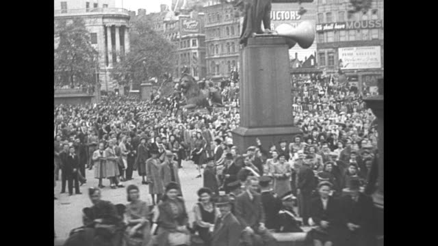 crowds wave in trafalgar square in london as sign in background reads victory over germany 1945 / troops ride on tank as it moves on road allied... - ve day stock-videos und b-roll-filmmaterial