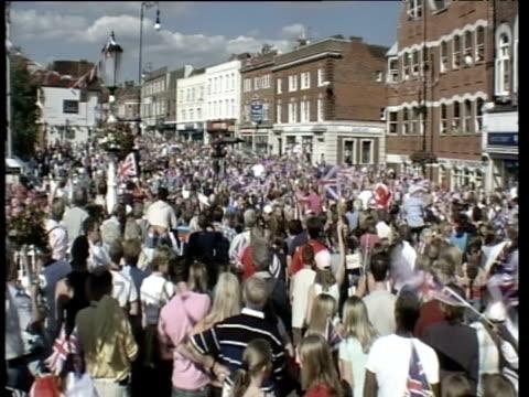 vídeos de stock e filmes b-roll de crowds waving union jacks on streets of tonbridge waiting for arrival of kelly holmes to mark her success in beijing 2008 olympics - bandeira da grã bretanha
