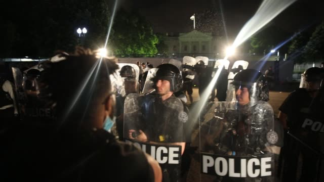 vidéos et rushes de crowds with force move against the barriers and toss water towards the police behind protective shields as demonstrators hold a protest in response... - police force