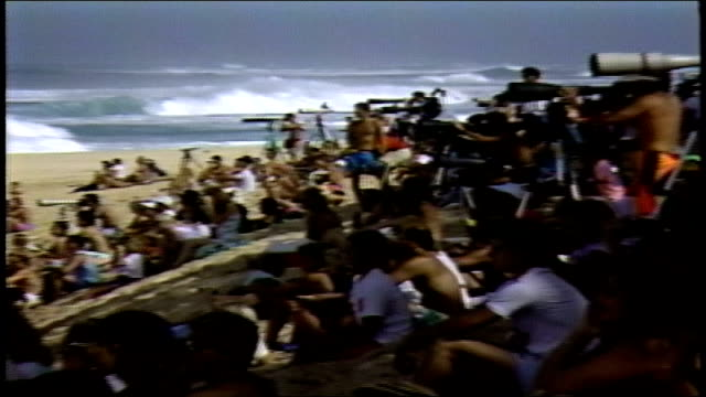 crowds with large zoom lenes on beach watching water in pupukea hawaii - contestant stock videos & royalty-free footage