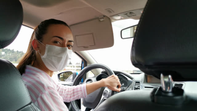 crowdsourced female taxi driver wearing a facemask while looking at camera - passenger stock videos & royalty-free footage