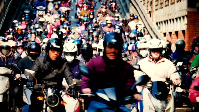 crowed of people are riding scooters, traffic on the bridge through city - crash helmet stock videos and b-roll footage