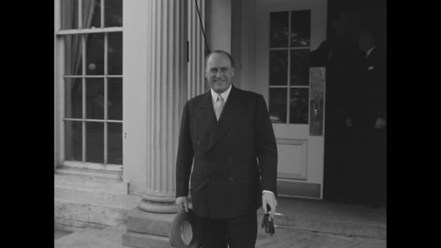 Crown Prince Olav of Norway smiles as he stands outside the White House during his visit to Washington DC he holds his hat and a cigarette / 2shot...