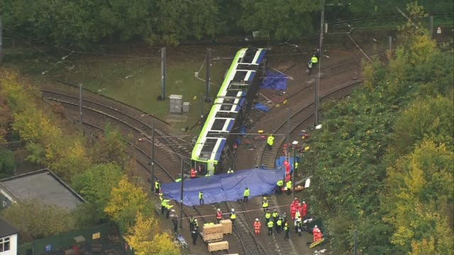 Aerials of scene AIR VIEWS More of overturned tram and emergency workers at scene / blue tarpaulin being moved into place by emergency workers