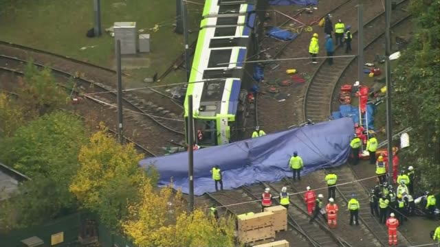 Report finds driver may have had 'microsleep' LIB ENGLAND London Croydon of derailed tram and emergency workers or investigators at scene END LIB
