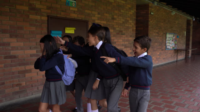 cruel group of kids at school bullying a little girl covering her face with hands - bullying stock videos & royalty-free footage