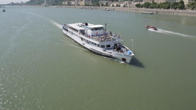 cruise boat sailing under chain bridge szechenyi lamchid,& river danube, budapest, hungary, europe - ponte con catene ponte sospeso video stock e b–roll