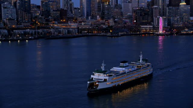 aerial cruise ferry with seattle in the background at night - nave video stock e b–roll
