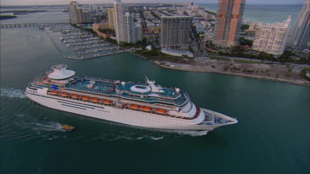 AERIAL WS Cruise ship leaving harbor via Government Cut at sunset / Miami Beach, Florida, USA