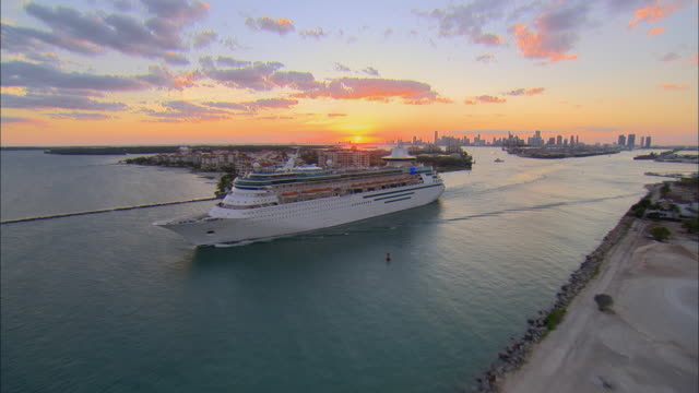 aerial ws cruise ship leaving harbor via government cut at sunset / miami beach, florida, usa - kreuzfahrtschiff stock-videos und b-roll-filmmaterial