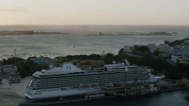 WS AERIAL POV Cruise ship moored in port at sunset / Old San Juan, San Juan, Puerto Rico, United States