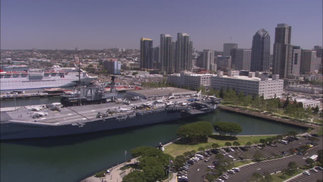 vídeos de stock e filmes b-roll de a cruise ship moors near the uss midway aircraft carrier in san diego, california. - uss midway