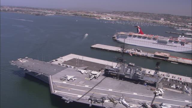 vídeos de stock e filmes b-roll de a cruise ship moors near the uss midway cv-41 in san diego, california. - uss midway