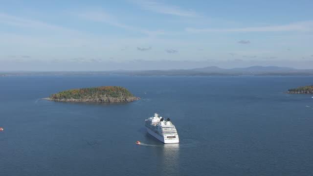 ws aerial pov cruise ship moving on bay against blue sky/ bar harbour, maine, united states - bar点の映像素材/bロール